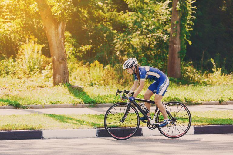 Female Cyclist Rides A Racing Bike On Road - Best Bike Shorts for Women