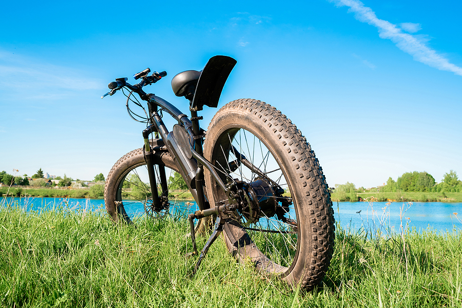 Black Electric Bike With Thick Wheels On The Grass Near The Lake - Electric Bike Accessories