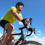 Best cycling gloves. Biking man cycling on road bike traveling in summer doing ecotou