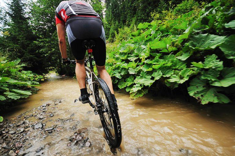 Best mountain bike shoes. young man drive mountain bike over water river